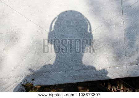 The Shadow Of A Man's Head With Headphones On Old Canvas Tarps