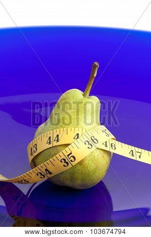 Pear fruit and tape measure on a platter
