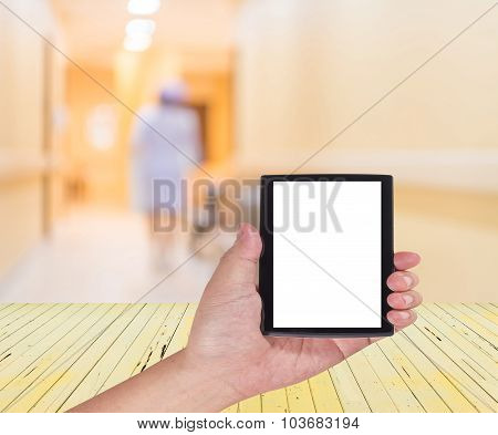 Male Hand Is Holding A Modern Touch Screen Phone  And Blur Image Of Nurse In Hospital Walkway .