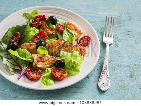 Fresh Salad With Chicken Breast, Sun-dried Tomatoes, Green Salad And Olives On A White Plate On A Wo