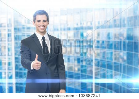 Businessman who thumbs up on blue background. Concept of leadership and success