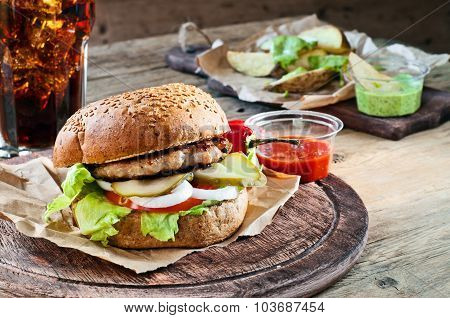 Fresh Burger With Sauce And Potatoes On A Rustic