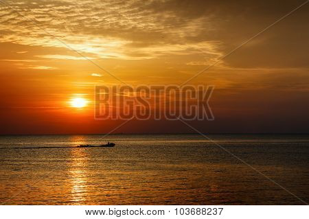 Silhouette Of A Man On A Jet Ski In The Sea At Sunset.