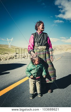 A Tibetan farmer with her kid in a steppe in Tibet, China