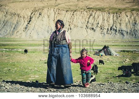 A Tibetan farmer with her kid in a steppe in Tibet, China.