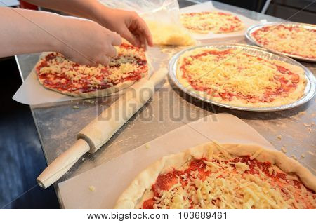 Hands Spreading Cheese On Pizza