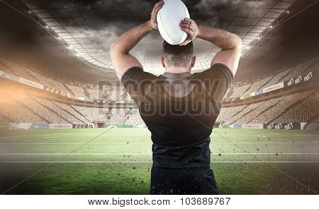 Tough rugby player throwing ball against rugby stadium
