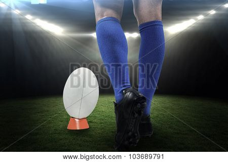 Low section of rugby player about to kick the ball against rugby stadium