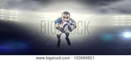 Portrait full length of American football player diving against spotlight