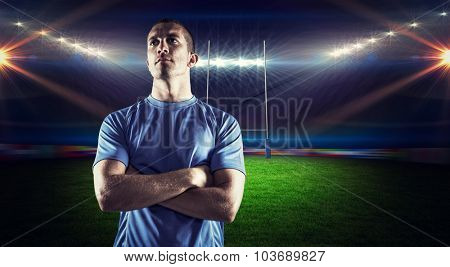 Confident rugby player looking away with arms crossed against rugby stadium