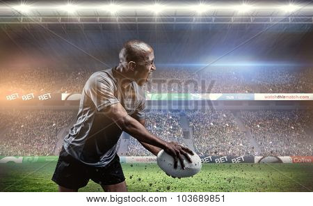 Sportsman playing rugby against rugby stadium