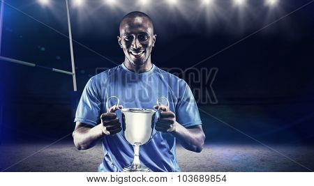 Portrait of happy athlete holding trophy against rugby stadium