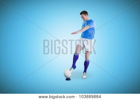 Rugby player doing a drop kick against blue background with vignette