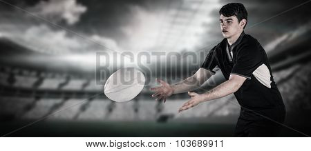 Rugby player throwing a rugby ball against rugby arena