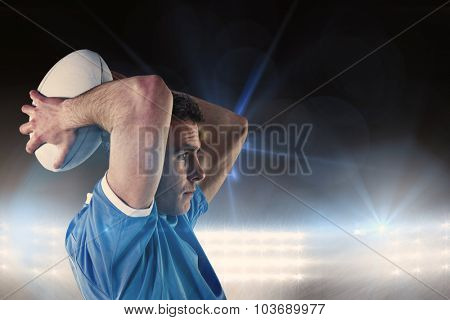 Rugby player gesturing with hands against spotlights