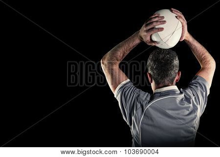 Rugby player about to throw a rugby ball against black