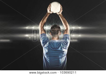Rear view of sports player throwing ball against spotlights
