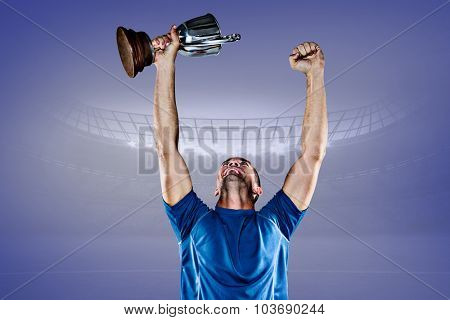 Happy rugby player holding trophy against purple vignette