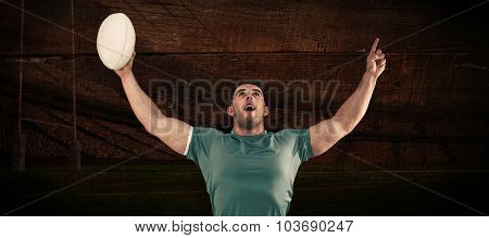 Rugby player cheering and pointing against rugby stadium