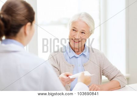 medicine, age, health care and people concept - doctor giving prescription to happy senior woman at hospital