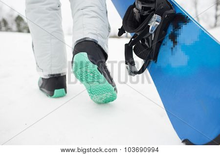 winter, leisure, sport and people concept - close up of snowboarder legs walking with snowboard outdoors