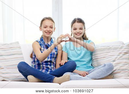 people, children, friends and friendship concept - happy little girls sitting on sofa and showing heart shape hand sign at home
