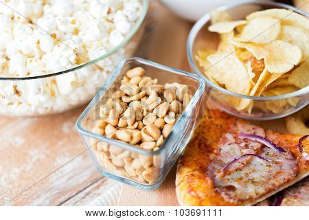 fast food and unhealthy eating concept - close up of peanuts in glass bowl, potato chips, pizza and popcorn on wooden table