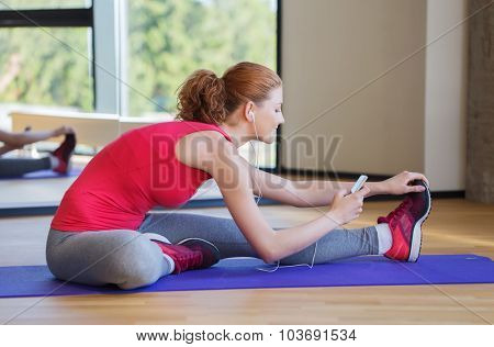 fitness, sport, people, technology and lifestyle concept - smiling woman with smartphone and earphones stretching in gym
