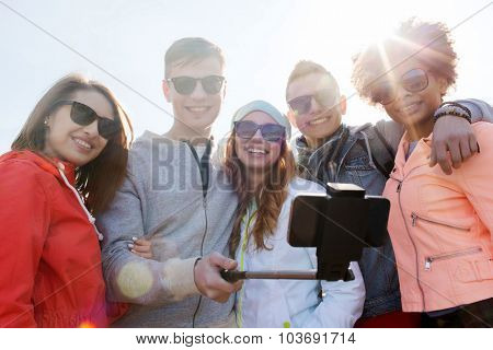 people, leisure, friendship and technology concept - group of smiling teenage friends taking picture with smartphone on selfie stick outdoors