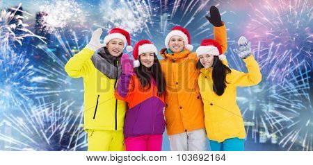 winter holidays, christmas, friendship and people concept - happy friends in santa hats and ski suits outdoors over firework background