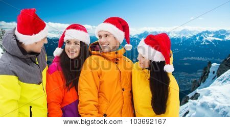 winter holidays, christmas, friendship and people concept - happy friends in santa hats and ski suits talking outdoors over snowy mountains background