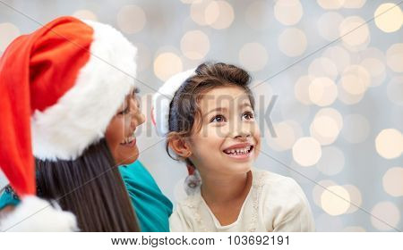 christmas, holidays, family, childhood and people concept - happy mother and little girl in santa hats over lights background