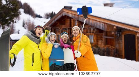 winter sport, leisure, friendship, technology and people concept - happy friends with snowboards and taking picture by smartphone on selfie stick over wooden country house background and snow