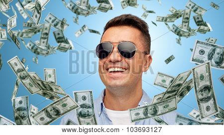 business, finance, success and people concept - face of smiling middle aged latin man in shirt and sunglasses over blue background with heap of falling dollar money