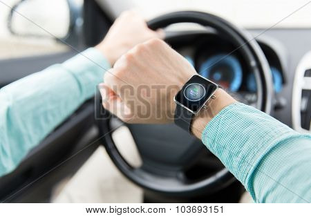 transport, business trip, technology, time and people concept - close up of man with engine start button on smart watch driving car
