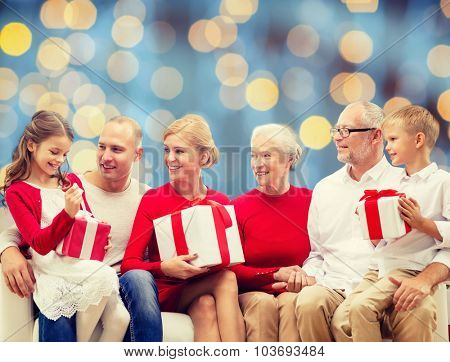 family, holidays, generation, christmas and people concept - smiling family with gift boxes sitting on couch over blue lights background