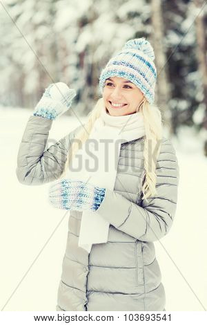 season, christmas and people concept - happy smiling young woman throwing snowball in winter forest