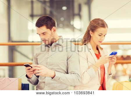sale, consumerism, technology and people concept - young couple with shopping bags and smartphones in mall