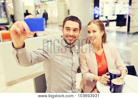 sale, shopping, consumerism, technology and people concept - happy young couple with smartphone taking selfie at cafe in mall