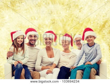 family, happiness, generation, holidays and people concept - happy family in santa helper hats sitting on couch over yellow lights background