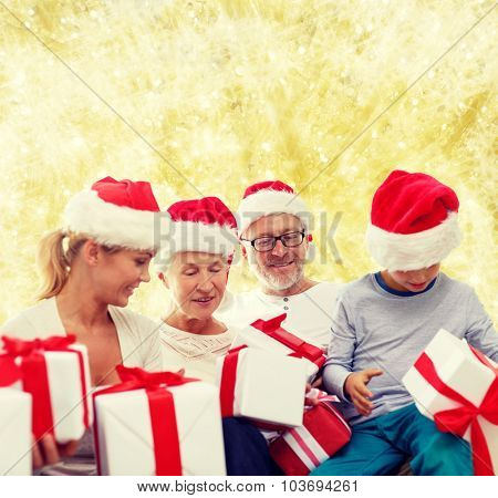 family, christmas, generation, holidays and people concept - happy family in santa helper hats with gift boxes sitting over yellow lights background