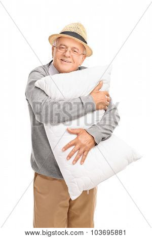 Vertical shot of a cheerful senior gentleman hugging a white pillow and looking at the camera isolated on white background