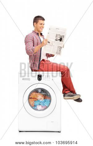 Vertical shot of a young man reading a newspaper while waiting for the washing machine to finish the laundry isolated on white background