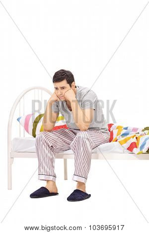 Vertical shot of a worried young man in pajamas sitting on a bed and contemplating isolated on white background