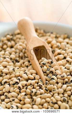 uncooked beans and wooden scoop in bowl