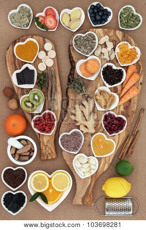 Large super food and medicinal herb selection for cold remedy with foods high in antioxidants on olive wood boards over white background.
