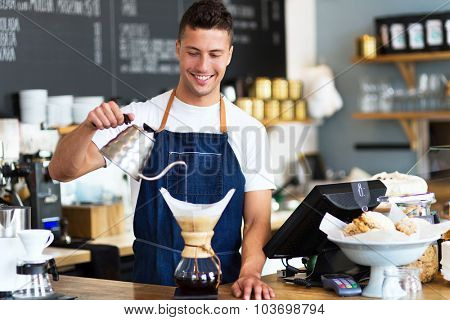 Barista pouring water into coffee filter