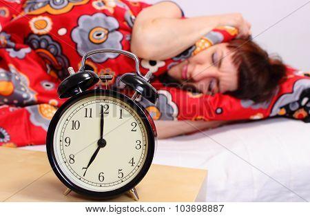 Brunette Woman Sleeping In Her Bedroom, Ringing Alarm Clock
