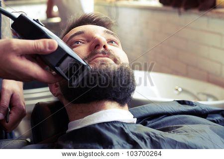 barber shaving beard with electric razor in vintage barber shop