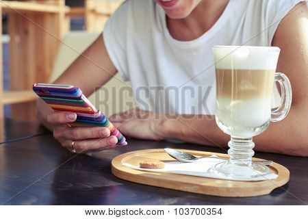 young female sitting in cafe and using smartphone